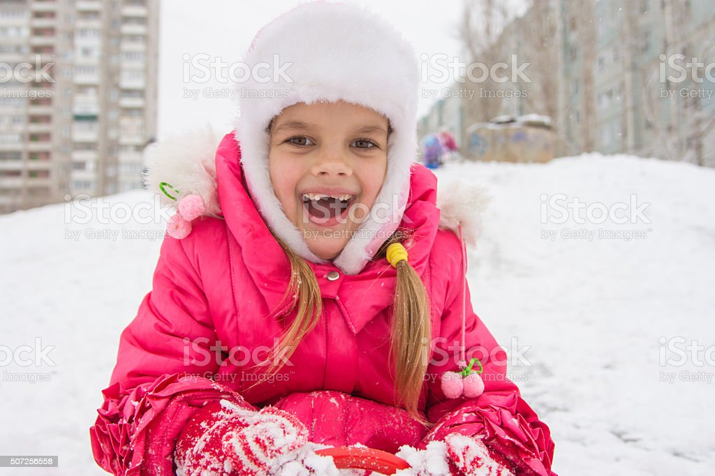The girl rolled down hill and looking happily into frame stock photo