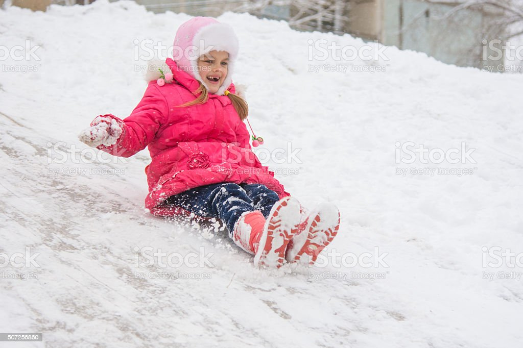 The girl rolled down the ice slide stock photo
