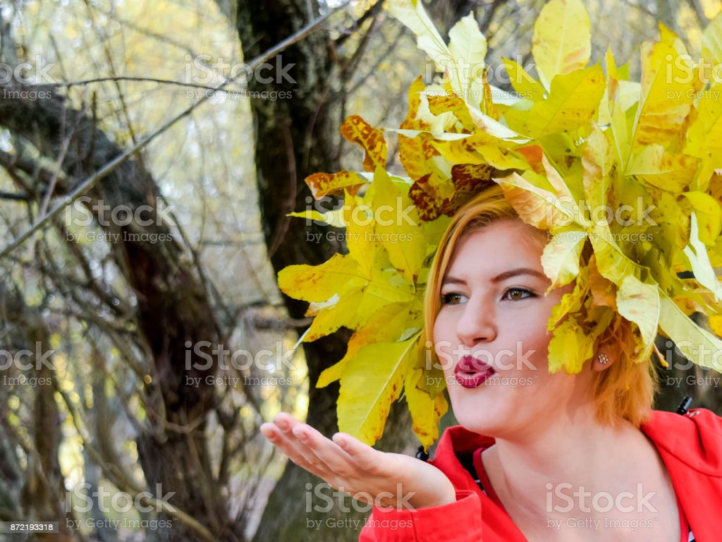 The girl sends an air kiss. Girl in a red jacket with a wreath of yellow autumn leaves. The Queen of Autumn. Miss autumn. Autumn Walk. stock photo