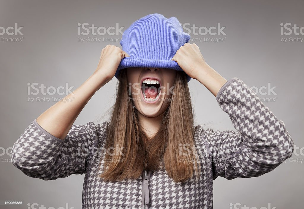 The girl shouts, having pulled a cap on eyes royalty-free stock photo