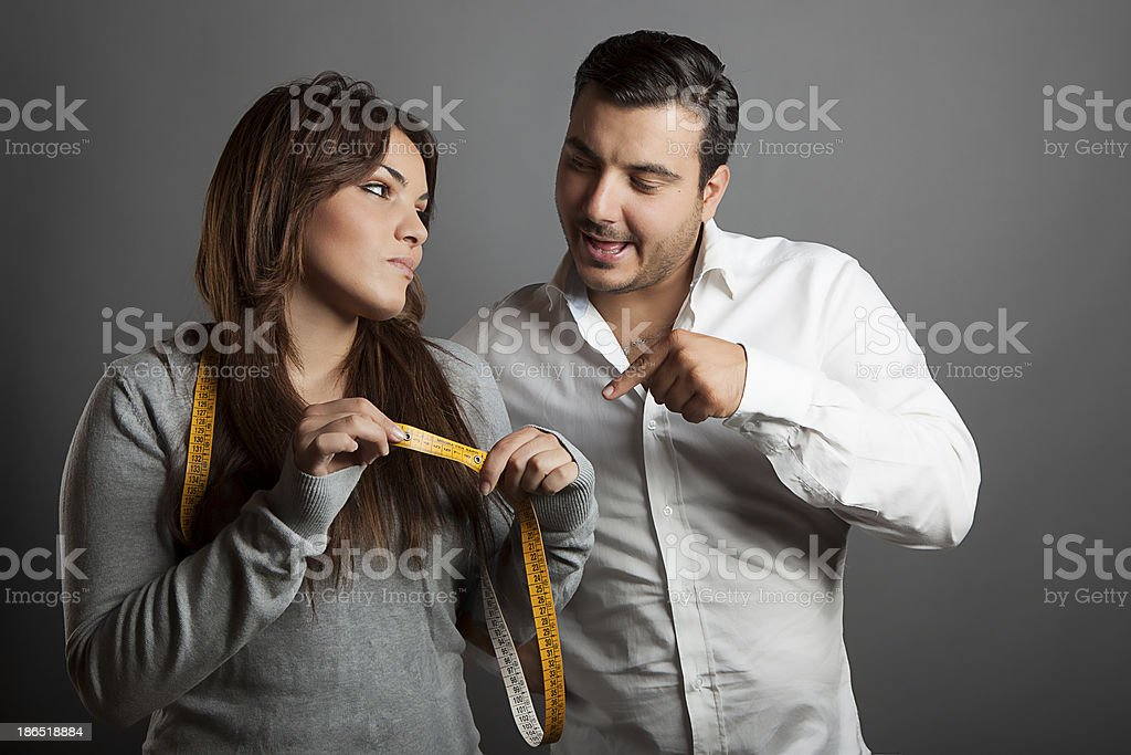 The girl showing to her boyfriend his sex length royalty-free stock photo