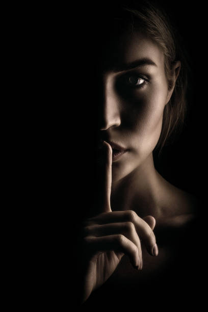 The girl shows a sign of silence. Face on black background, close-up The girl shows a sign of silence. Face on black background, close-up finger on lips stock pictures, royalty-free photos & images