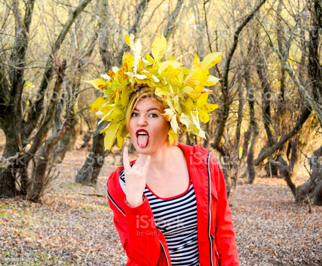 The girl shows her tongue. Girl in a red jacket with a wreath of yellow autumn leaves. The Queen of Autumn. Miss autumn. Autumn Walk stock photo