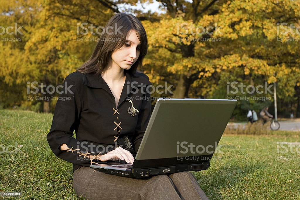 The girl sits at a notebook computer royalty-free stock photo
