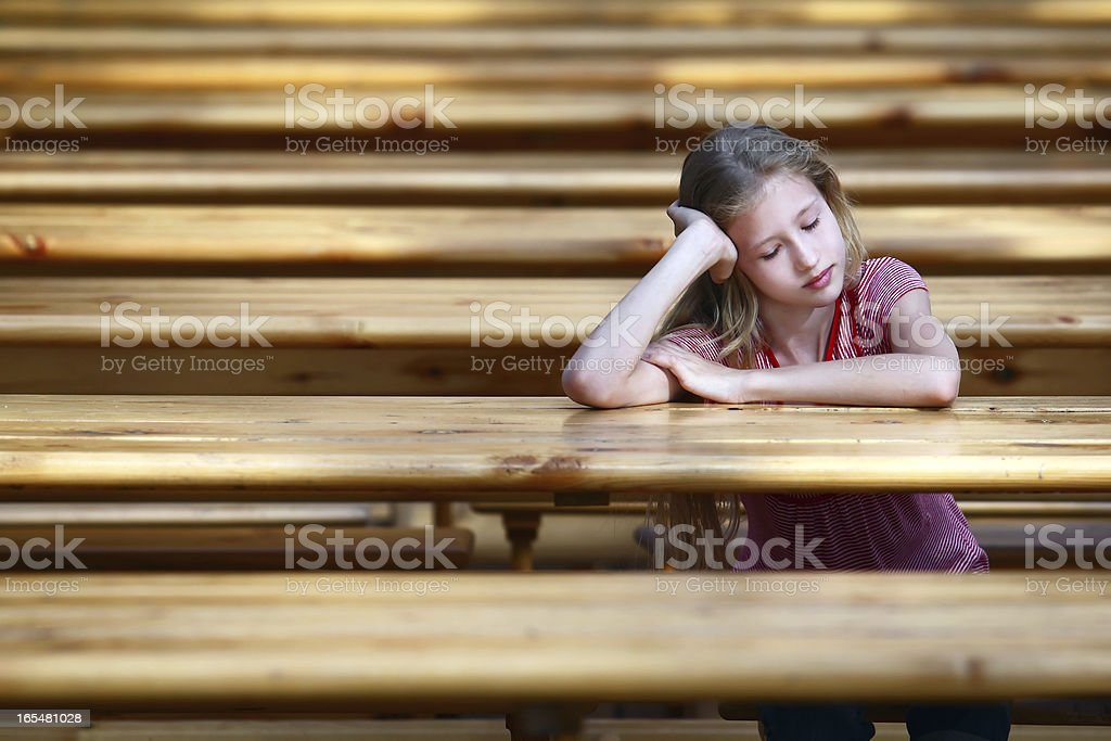 The girl sits at a table royalty-free stock photo