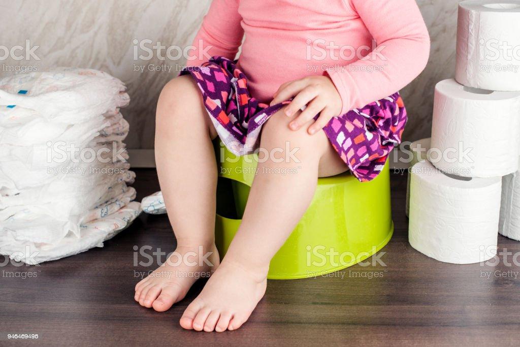 la chica se sienta en un bote verde y aprende básicas de higiene - foto de stock