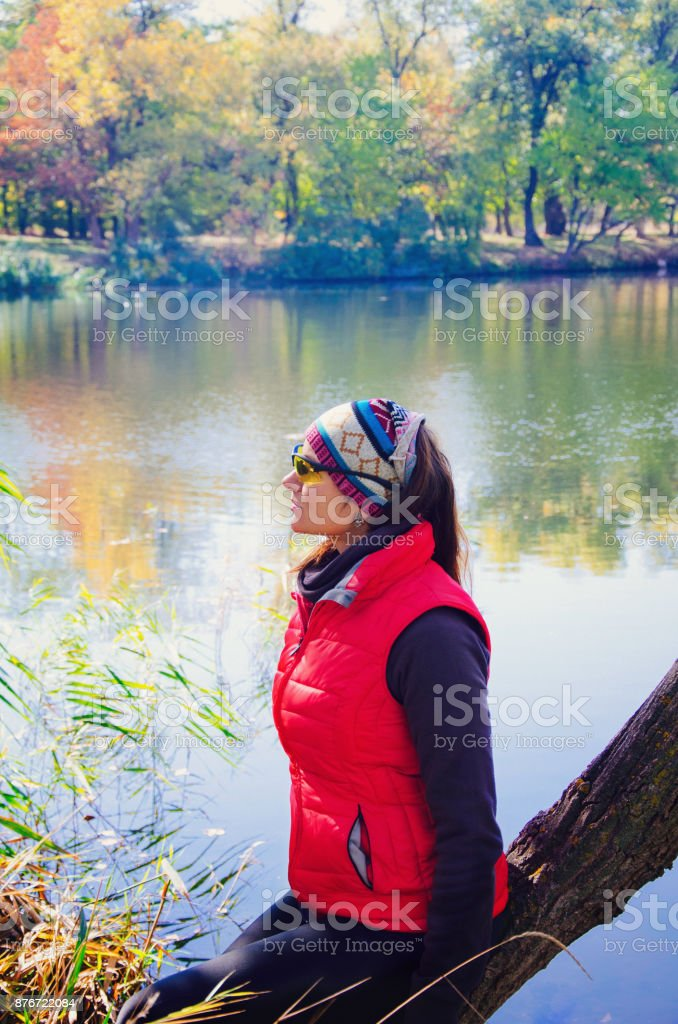 the girl sits on the river bank stock photo