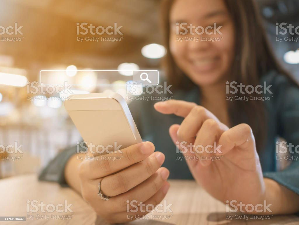 The Girl Smiles And Uses A Smartphone To Find What You Are Interested Searching Information Data On Internet Networking Concept Stock Photo Download Image Now Istock