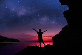 The girl standing on the rocks near the beach with beautiful million stars galaxy and red sky sunset.