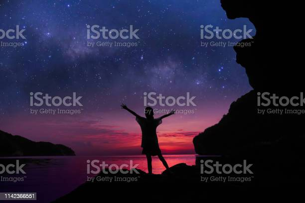 Photo of The girl standing on the rocks near the beach with beautiful million stars galaxy