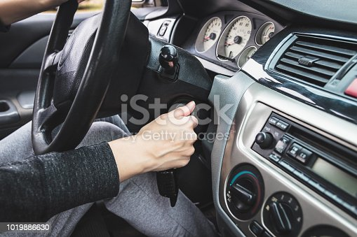 The girl starts the car by inserting the ignition key into the lock. Dashboard