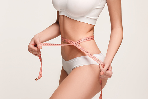 The girl taking measurements of her body, white studio background.