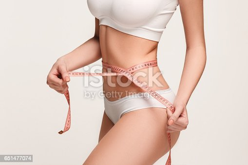 istock The girl taking measurements of her body, white background 651477074