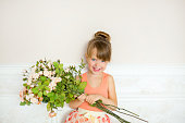 the little girl disguised as the ballerina costs with a bouquet of flowers and smiles