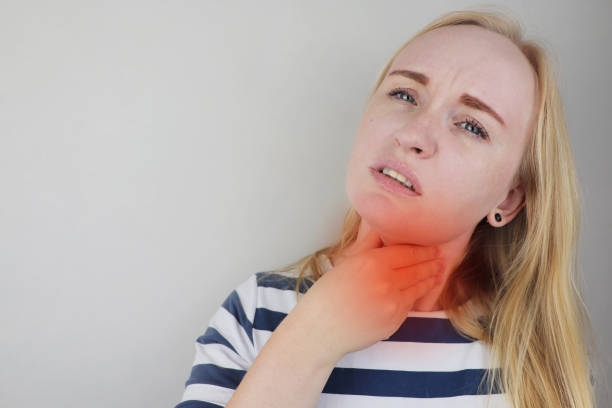 The girl touches the upper part of the neck. Pain is visible on her face. Inflamed lymph nodes due to the common cold, influenza virus, or coronovirus. Pain is visible on her face. Inflamed lymph nodes due to the common cold, influenza virus, or coronovirus. The girl touches the upper part of the neck. heartburn throat pain stock pictures, royalty-free photos & images