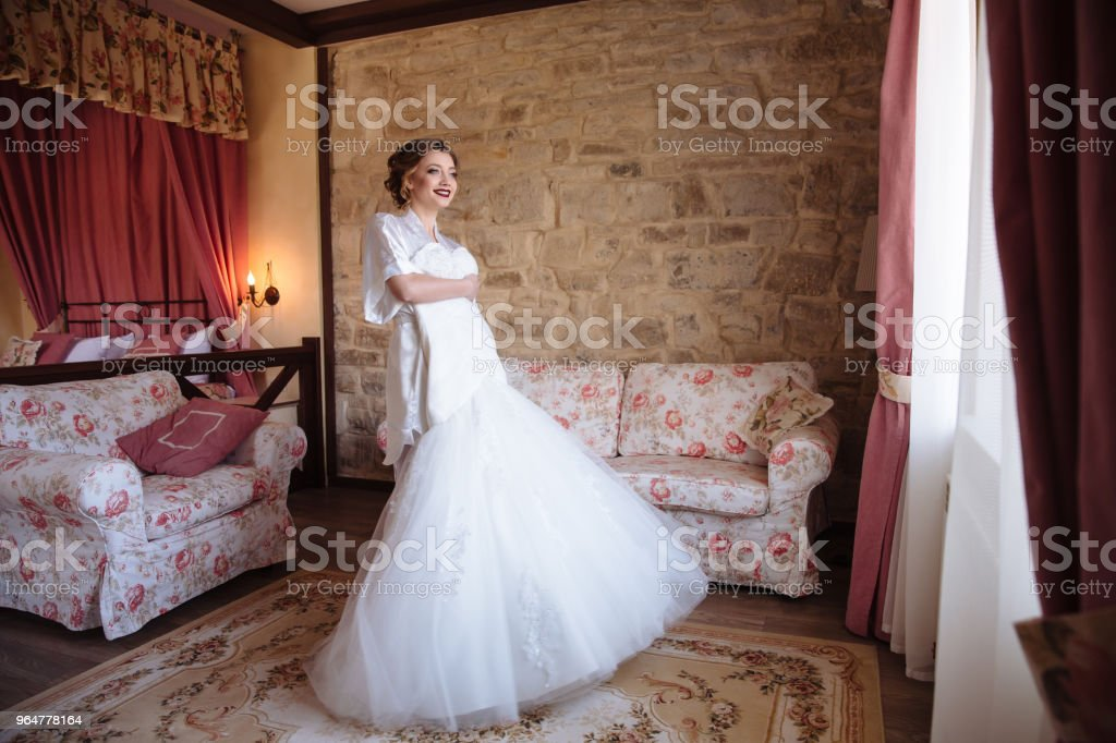 The girl tries on a wedding dress and flaunts in her room. The bride is smiling looking out the window royalty-free stock photo