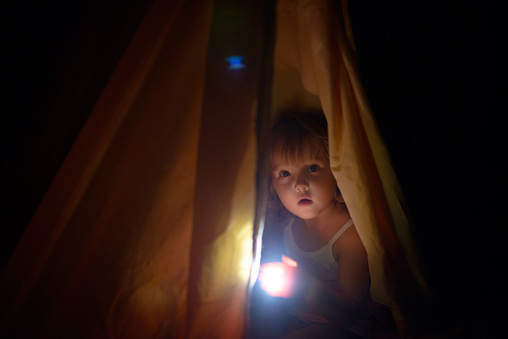 The girl under a cover holds at dark night a small lamp in hand