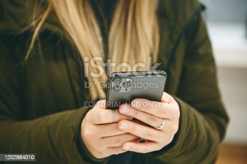 599114758 istock photo The girl uses a new cell phone 1202884010