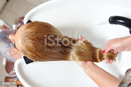 The girl washes her hair in a hairdresser, after painting her hair. Blonde.