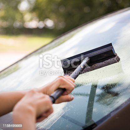 The girl washes the windshield of the car at a gas station. The glass is covered with a large number of dead insects and flies. The car after a trip on the autobahn is preparing to wash.