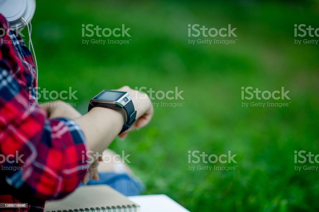 The girl watches the watch in hand, watches the time in a black...
