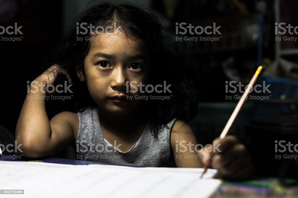 The girl who is writing a book in the dark with despair. stock photo