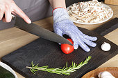 The girl with a knife cuts a tomato on a cutting board