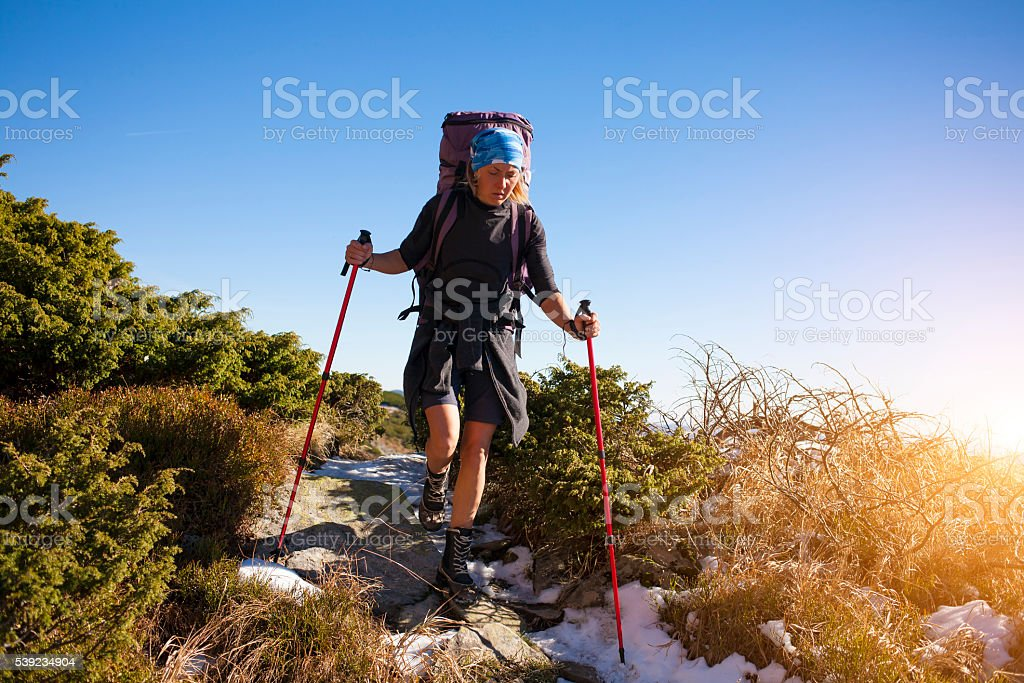 The girl with the backpack goes on the track. royalty-free stock photo