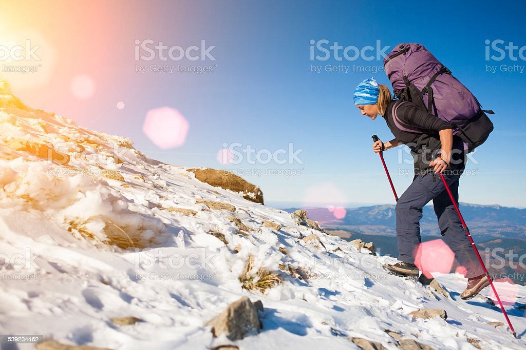 The girl with the backpack is on the slope. royalty-free stock photo