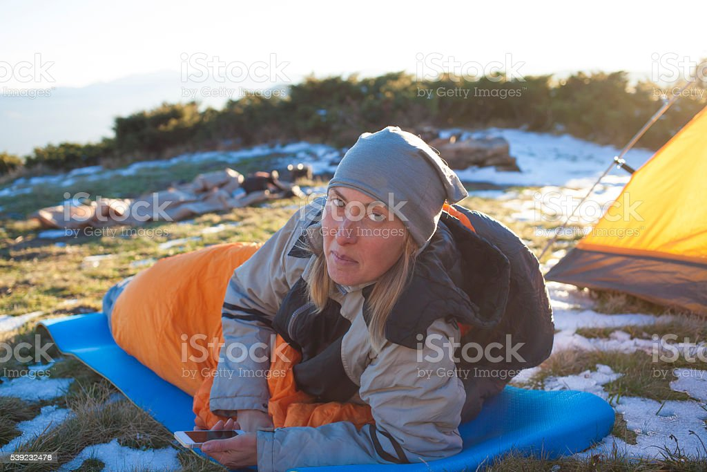 The girl with the phone lying in a sleeping bag. royalty-free stock photo