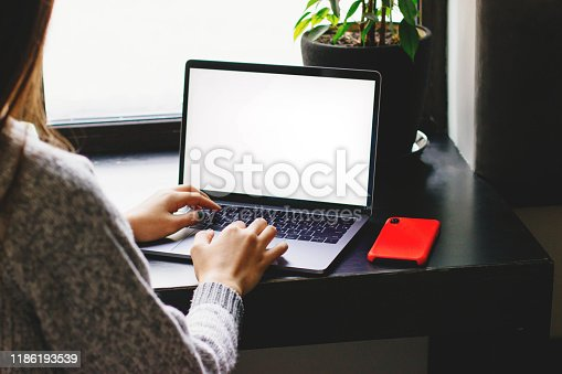 The girl works at the computer in a cafe. A laptop with a white screen sits on a table by the window. The girl holds a smartphone in her hands.