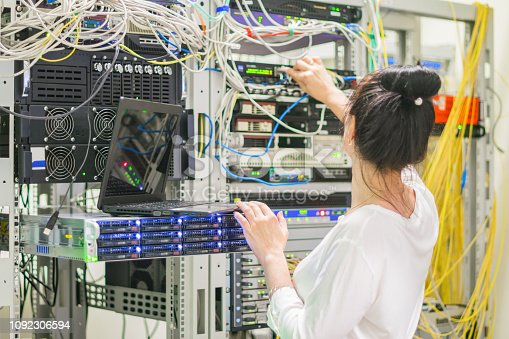 istock The girl works in the server room.The woman switches the wires in the datacenter. 1092306594
