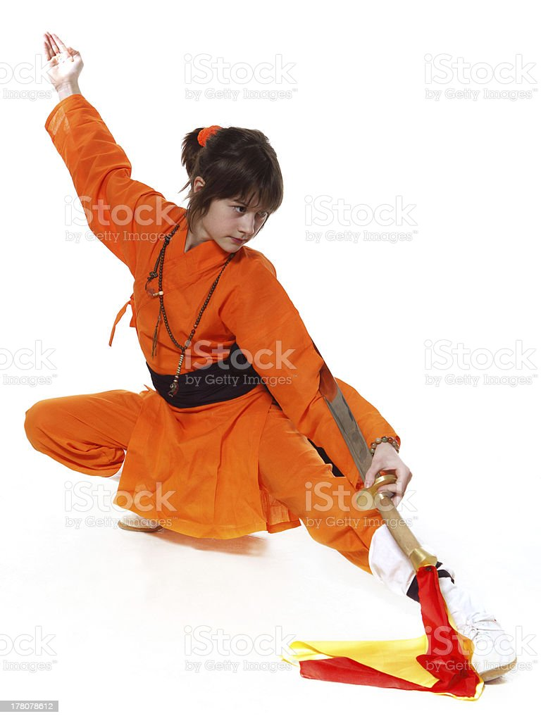 The girl wushu in orange costume on low pose stock photo