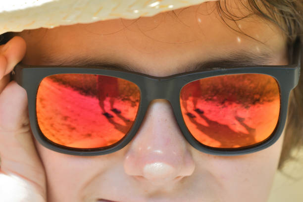 The girl's face and the reflection of a man with a camera in her sunglasses stock photo
