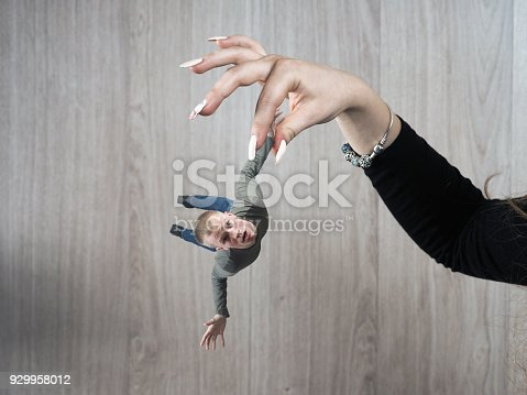 istock The girl's hand in disgust holds a frightened little man 929958012