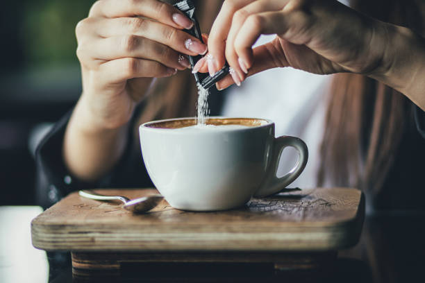 the girl's hand pours sugar into her coffee. close up - sweeteners stock photos and pictures