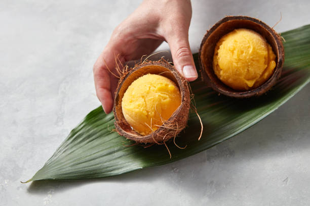 The girl's hand takes a coconut shell with mango ice cream on a gray beton background. Top view stock photo