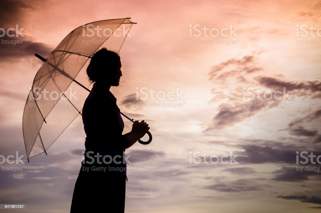 The girls silhouette style walking alone outdoor and umbrella in her hand with cloudy skies and evening sun stock photo