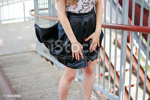 The girl's skirt rises in the wind. Black leather skirt