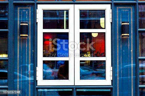 The glass facade of the building is blue with a white window and luminous decorative lanterns in black.