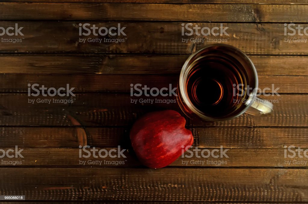 The glass of an apple cider vinegar and one red half of the apple. stock photo