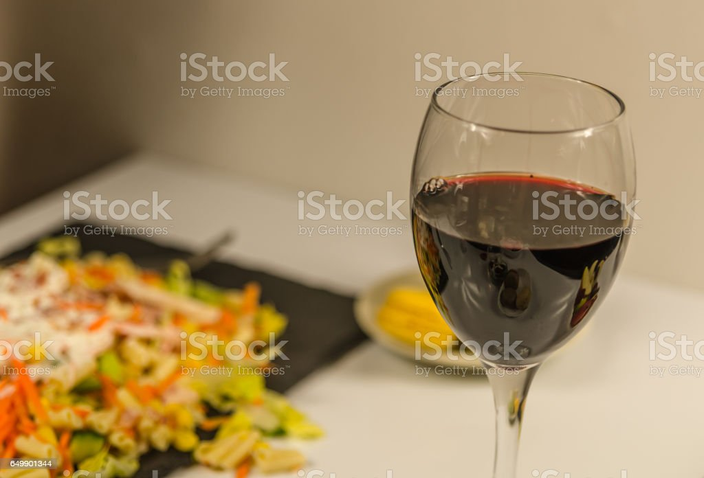 The glass of fine red wine in the background salad with bacon and chicken, dinner in restaurant stock photo