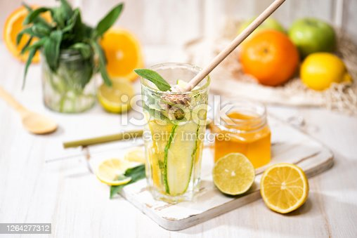 The glass of fresh lemonade with a honey. Beverage with lemon, sage, orange, and ice on the light wooden background. Summer cold drink or cocktail