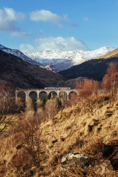The Glenfinnan Viaduct on a sunny spring day The Glenfinnan Viaduct - railway viaduct, located at the top of Loch Shiel in the West Highlands of Scotland. The viaduct overlooks the Glenfinnan Monument and the waters of Loch Shiel inverness scotland stock pictures, royalty-free photos & images