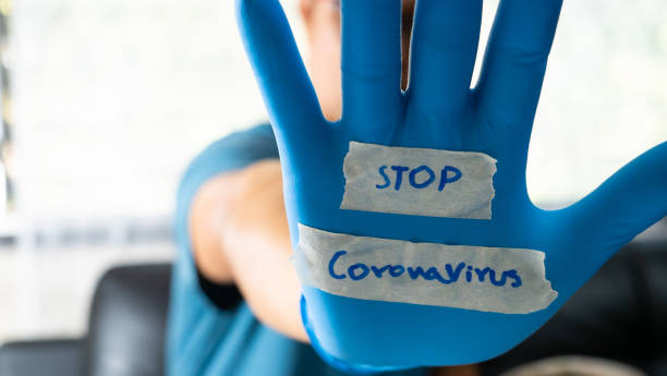 the glove-wearer has a message to stop the coronavirus - stop sign stock pictures, royalty-free photos & images