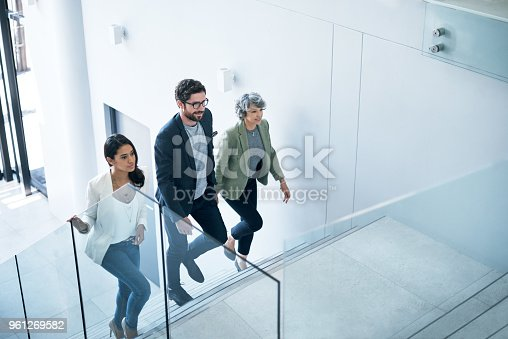Shot of a group of businesspeople walking up a staircase in an office