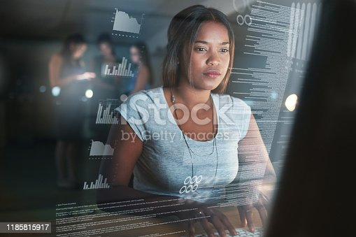 Cropped shot of an attractive young female programmer working on a computer code at night with her colleagues in the background