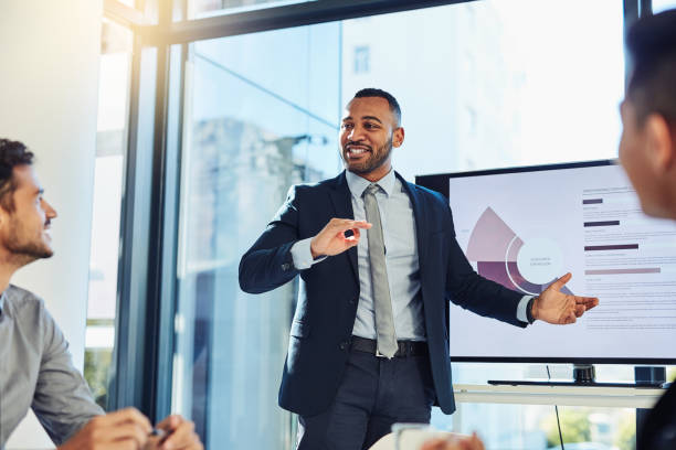 The goal was to grow and we did it Shot of a young businessman delivering a presentation to his colleagues in the boardroom of a modern office diad stock pictures, royalty-free photos & images
