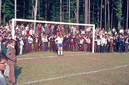 Berlin (West), Germany, 1967. Penalty shootout. A player must act as a goalkeeper in a penalty shootout. Young and old spectators crowd around the football goal. Unfortunately, it's not known how the penalty shoot-out went.