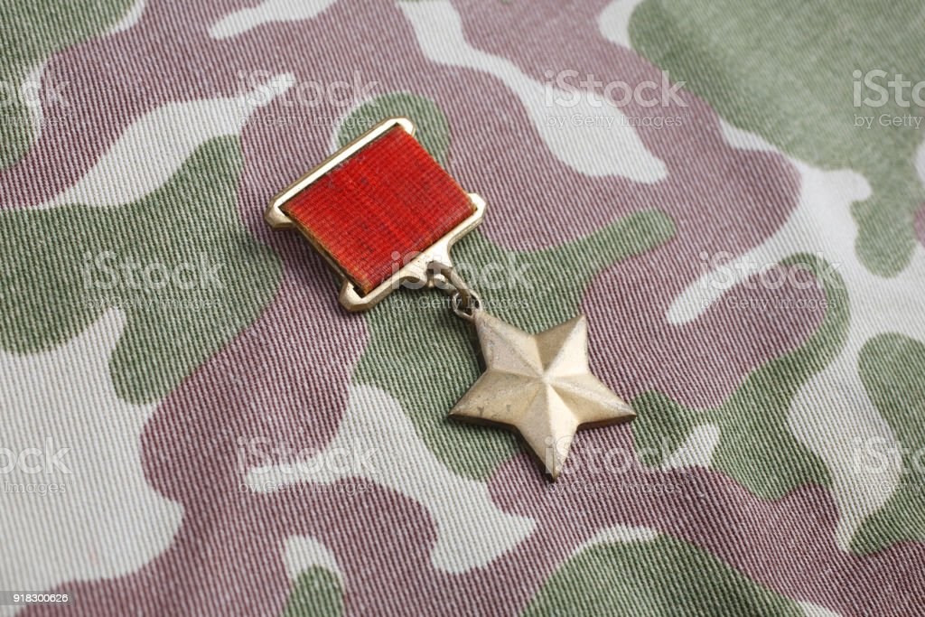 The Gold Star medal is a special insignia that identifies recipients of the title 'Hero' in the Soviet Union on Soviet camouflage uniform stock photo